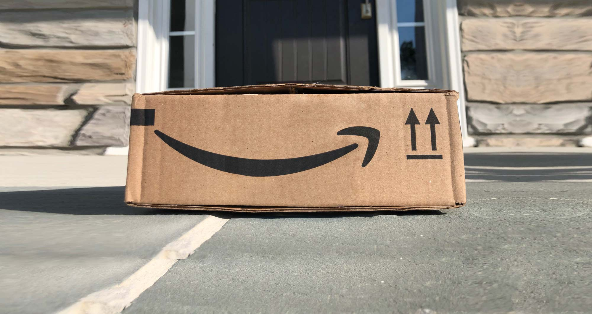 Amazon Prime shipping box that is sitting on the front porch of a home