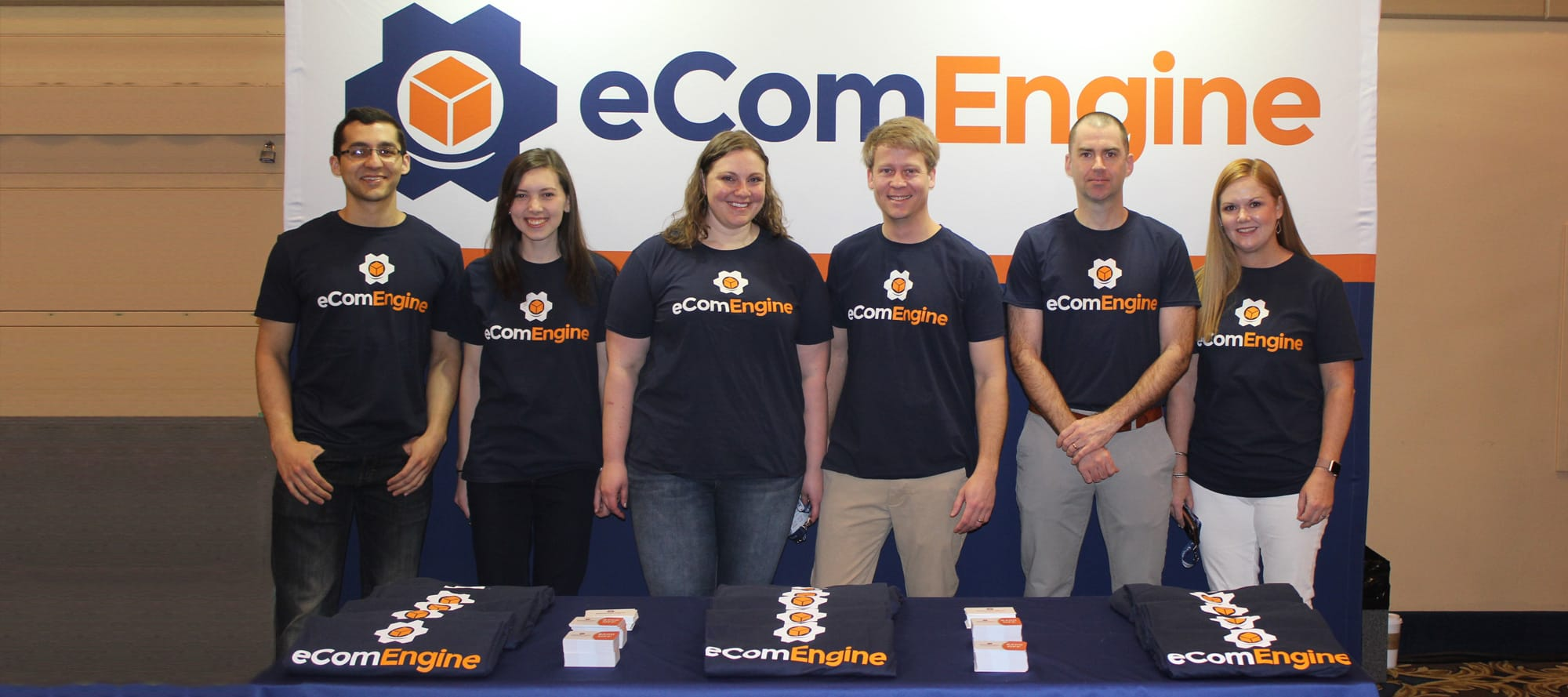 Six smiling eComEngine employees who are standing in front of a large eComEngine banner