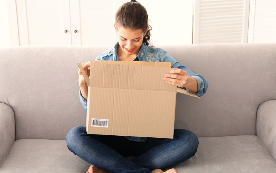 Happy Amazon buyer who is sitting on a couch and looking into a brown box